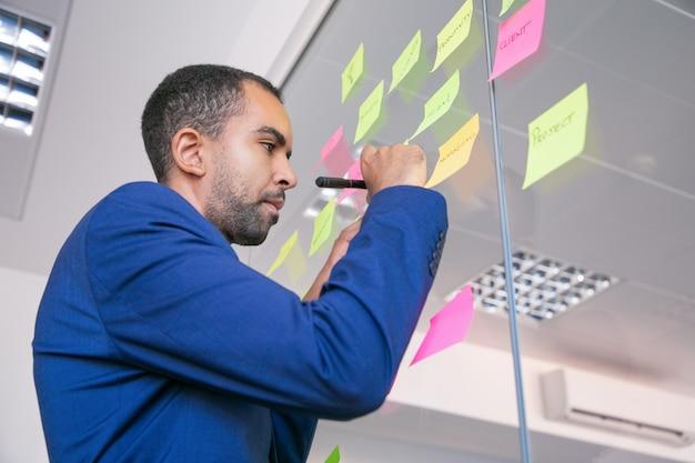 Afroamerikanischer büroarbeitgeber, der auf aufkleber mit markierung schreibt. konzentrierter, selbstbewusster geschäftsmann in der anzug-sharing-idee für das projekt und das notieren Kostenlose Fotos