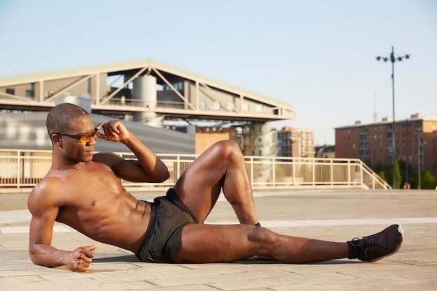 Afroamerikanischer mann, der das ausdehnen in städtische umwelt tut Premium Fotos