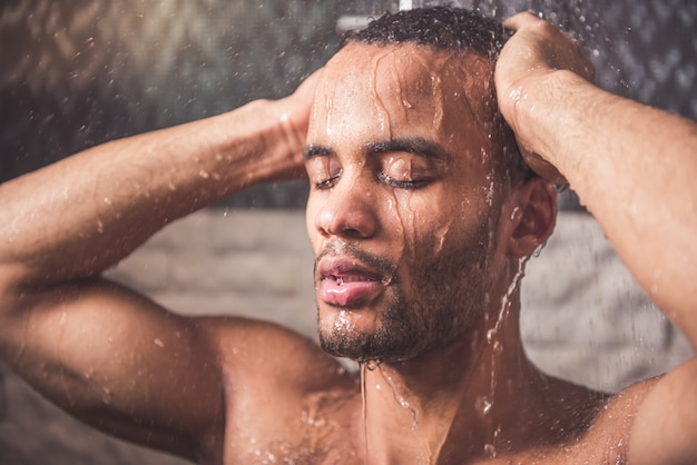 Afroamerikanischer mann duscht im badezimmer. Premium Fotos
