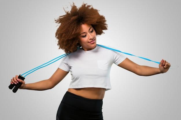 Afrofrau der jungen eignung, die ein springseil hält Premium Fotos