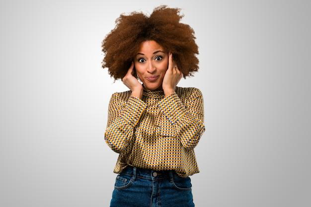Afrofrau, die ihre ohren abdeckt Premium Fotos