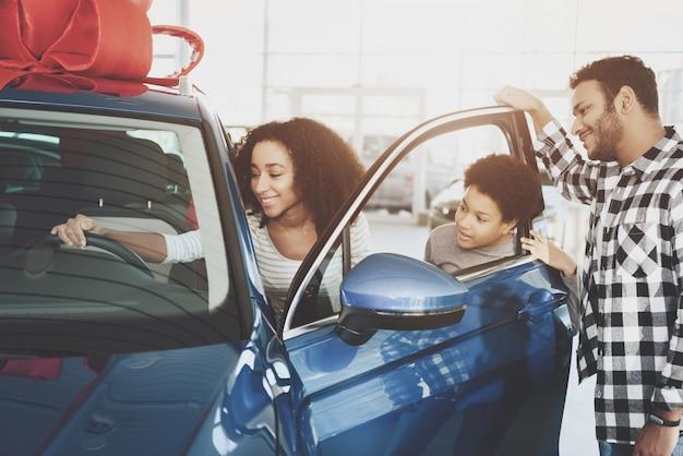 Afrofrau nimmt luxuriöses neues auto im ausstellungsraum. Premium Fotos