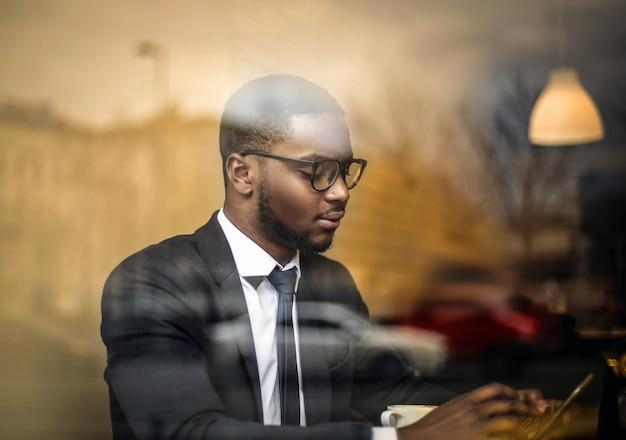 Afrogeschäftsmann, der seinen smartphone überprüft Premium Fotos