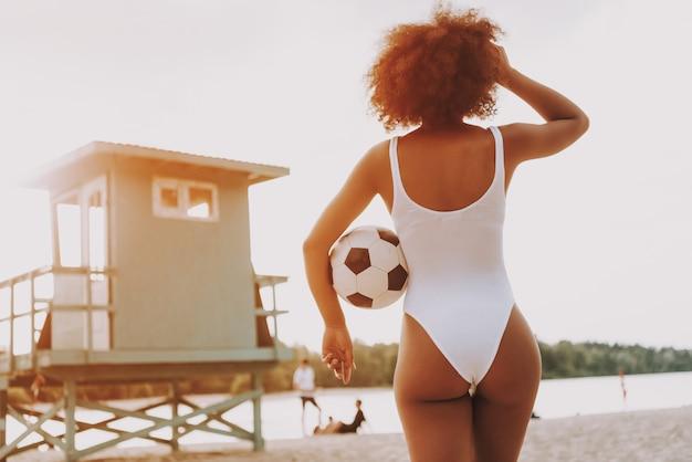 Afromädchen im sexy badeanzug, der durch strand schaut Premium Fotos