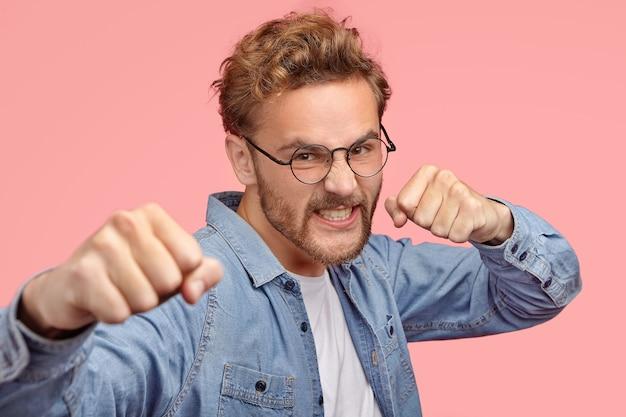 Aggressiver mann beißt mit fäusten, hat wütenden ausdruck, verteidigt sich, biss die zähne vor wut zusammen Kostenlose Fotos