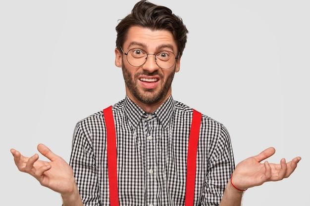 Ahnungsloser zögernder mann mit trendigem haarschnitt, trägt modisches outfit und brille, zuckt unsicher mit den schultern, trifft die wahl, isoliert über der weißen wand. konzept der menschen- und körpersprache Kostenlose Fotos