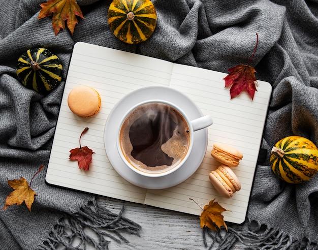 Ahornblätter, notizbuch, kaffeetasse und schal. herbst- oder winterkonzept. flache lage, draufsicht Premium Fotos