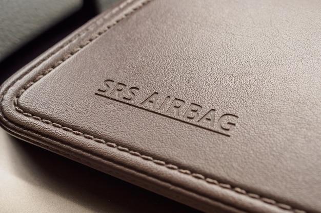 Airbag-sicherheitszeichen auf brauner lederbeschaffenheit im modernen auto Premium Fotos