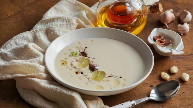 Ajo blanco, spanisch typische kalte suppe aus mandeln und knoblauch mit olivenöl und brot. Premium Fotos