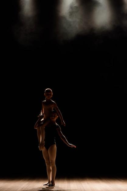 Akrobatischer tanz. tanz mit elementen der akrobatik. mädchen, die tanzunterstützung tun. Premium Fotos