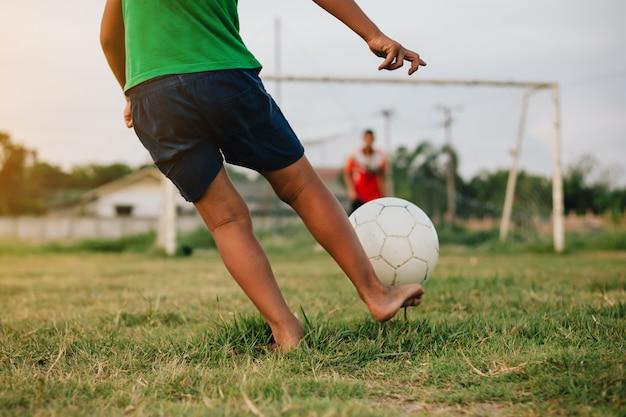 Aktionssport draußen einer gruppe kinder, die spaß haben, fußballfußball für übung zu spielen Premium Fotos