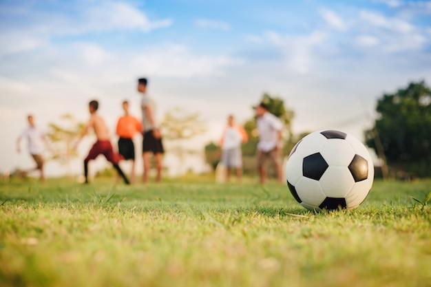 Aktionssport draußen von den kindern, die spaß haben, fußballfußball zu spielen Premium Fotos