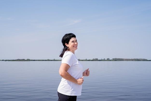 Aktive ältere frau, die nahe dem flussufer joggt Premium Fotos