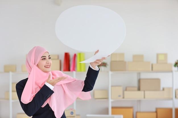Aktive asiatische muslimische frau im blauen anzug stehend und hält weiße sprechblase mit online-paketbox-lieferung Premium Fotos