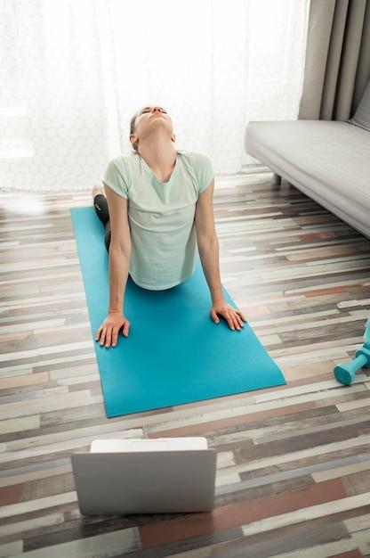Aktive frau, die yoga zu hause ausübt Kostenlose Fotos
