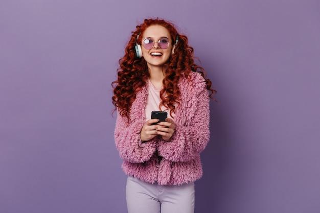 Aktive frau lacht beim musikhören in großen kopfhörern. mädchen in der rosa wolljacke und in der brille, die telefon hält. Kostenlose Fotos