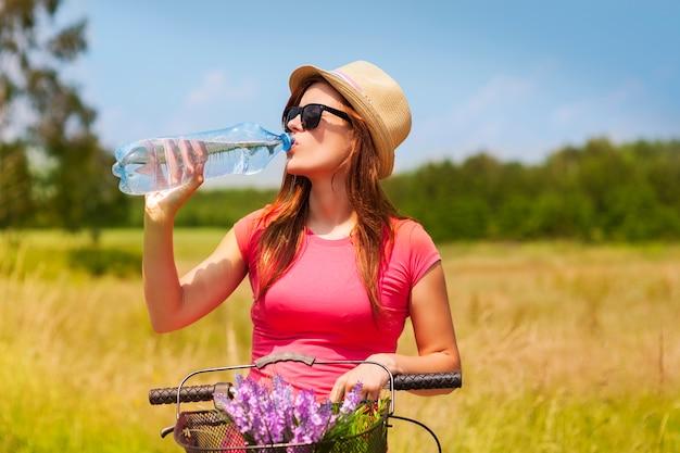 Aktive frau mit fahrrad, die kaltes wasser trinkt Kostenlose Fotos