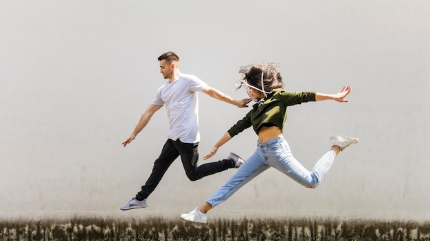 Aktive junge paare, die gegen schmutzwand springen Kostenlose Fotos