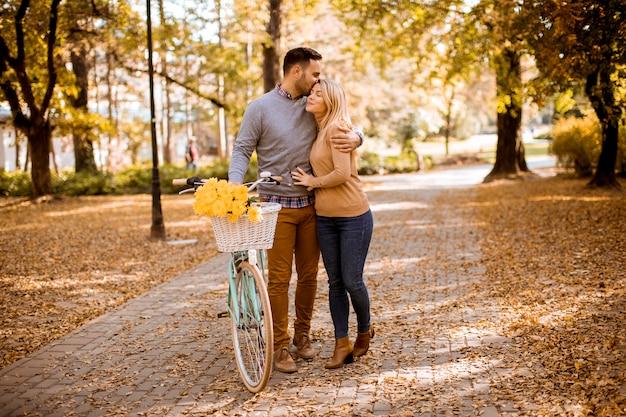 Aktive junge paare, die zusammen in reitfahrrad im goldenen herbstpark genießen Premium Fotos