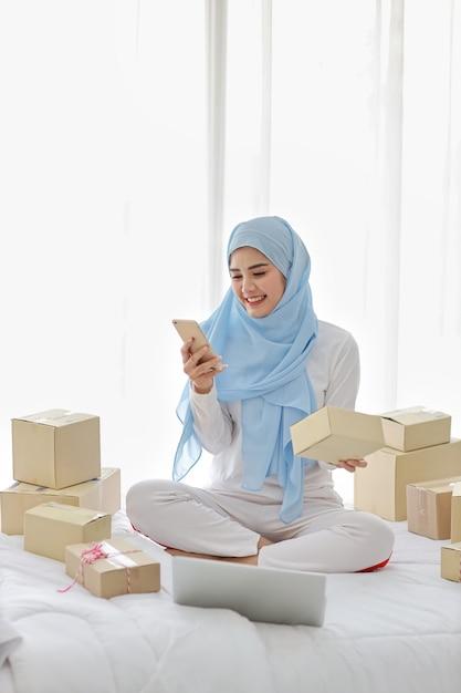Aktive lächelnde asiatische muslimische frau in der nachtwäsche, die auf bett mit handy und computer sitzt. freie freiberufliche kmu-frau des startups, die mit online-paketzustellung, e-commerce-konzept arbeitet. Premium Fotos