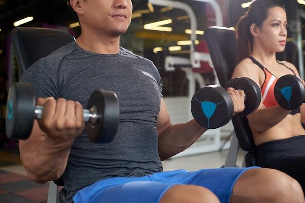 Aktive leute, die anhebendes gewicht der turnhallenübung tun Kostenlose Fotos