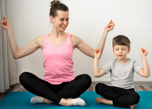 Aktive mutter praktiziert yoga mit ihrem sohn Kostenlose Fotos