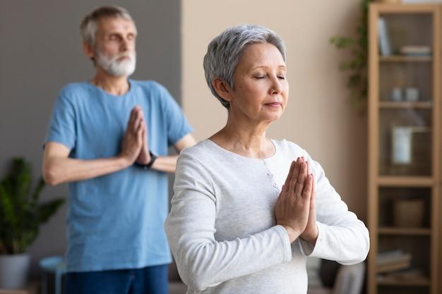 Aktive senioren, die zu hause yoga machen Kostenlose Fotos