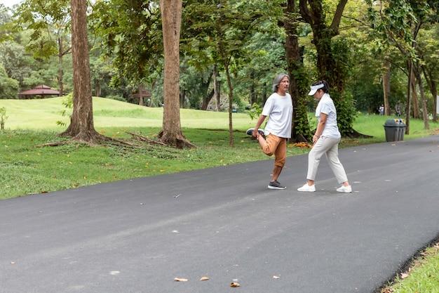 Aktiver asiatischer paarälterer in der sportkleidung, die am park rüttelt. Premium Fotos