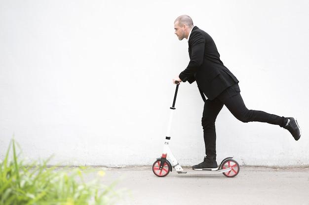 Aktiver geschäftsmann, der roller im freien reitet Premium Fotos