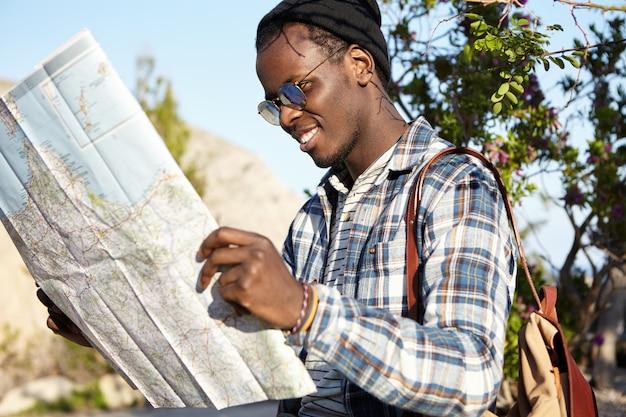 Aktiver lebensstil, reisen und tourismus. fröhlicher modischer junger dunkelhäutiger reisender mit rucksack, der karte hält, die über straßenfahrt im berggebiet in der naturumgebung aufgeregt fühlt Kostenlose Fotos