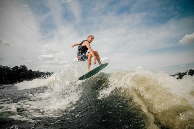 Aktiver mann, der auf die wellen des flusses springt Premium Fotos