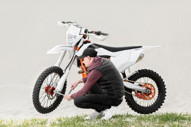 Aktiver mann, der versucht, motorrad zu reparieren Kostenlose Fotos