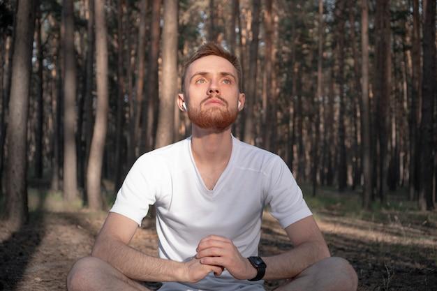 Aktiver mann sitzt im kiefernwald und genießt die meditation im freien Premium Fotos