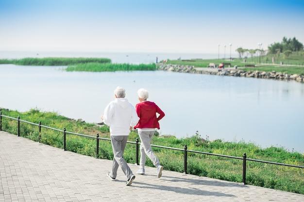 Aktives älteres paar, das entlang see läuft Premium Fotos