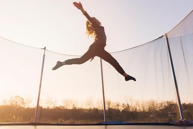 Aktives kleines mädchen, das über die trampoline gegen den himmel springt Kostenlose Fotos