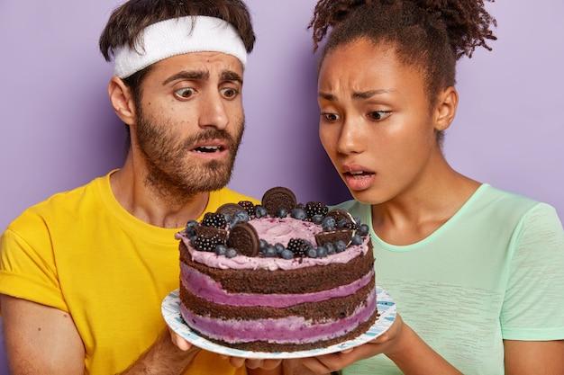 Aktives paar posiert mit einem großen kuchen Kostenlose Fotos