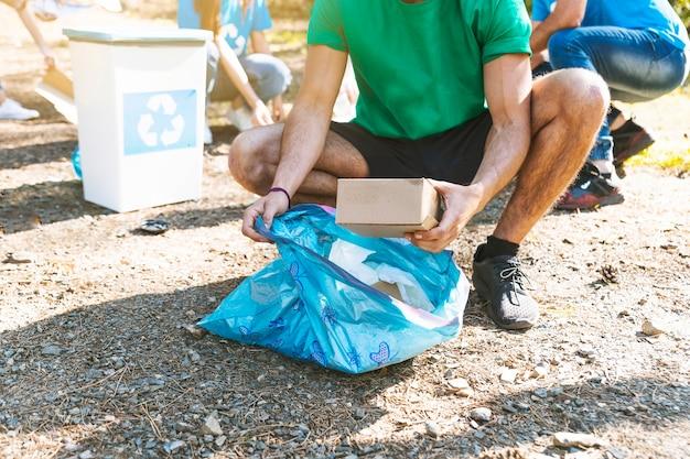 Aktivist, der abfall im abfallbeutel sammelt Kostenlose Fotos