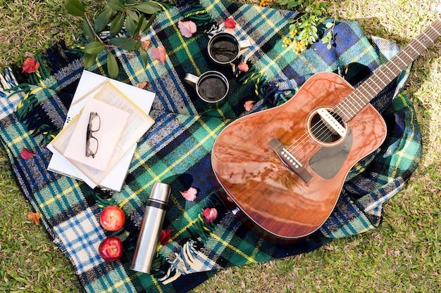 Akustikgitarre der draufsicht auf picknicktuch Kostenlose Fotos