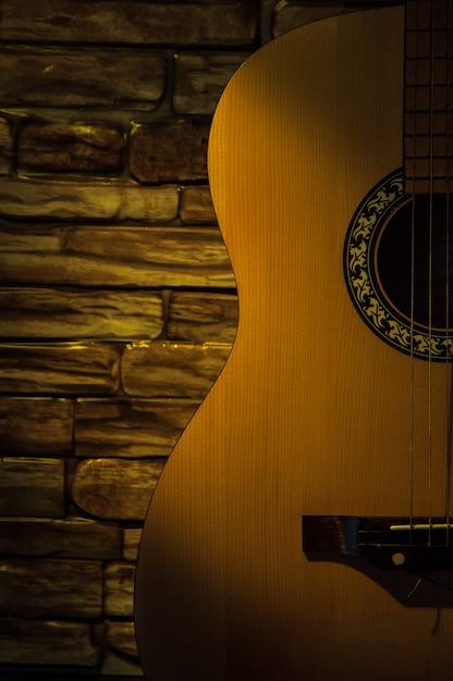 Akustikgitarre gegen eine backsteinmauer Premium Fotos