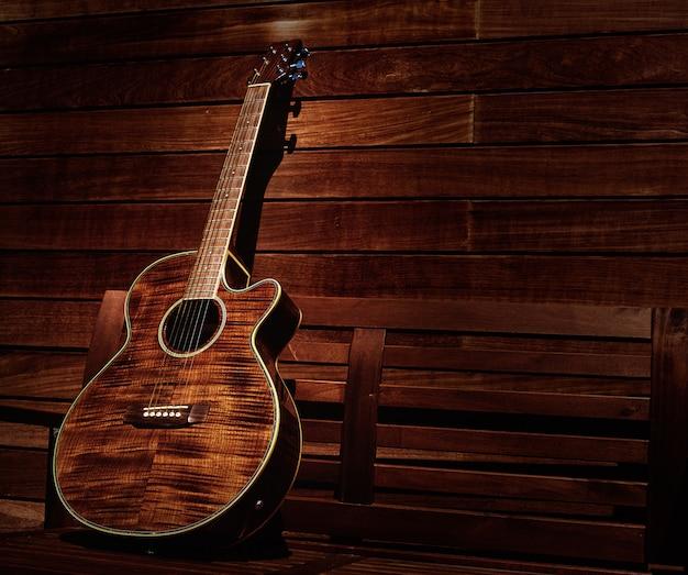 Akustische braune gitarre in holzstreifen Premium Fotos