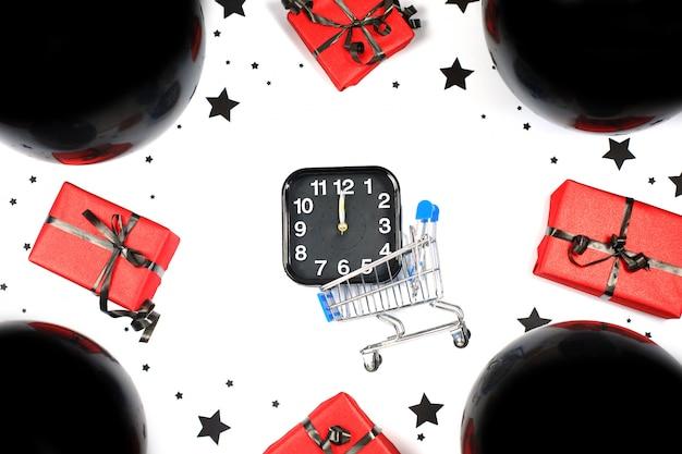 Alarm und mini-einkaufswagen mit schwarzen luftballons und geschenkboxen. einkaufs- und verkaufszusammensetzung. black friday verkauf. cyber montag. Premium Fotos