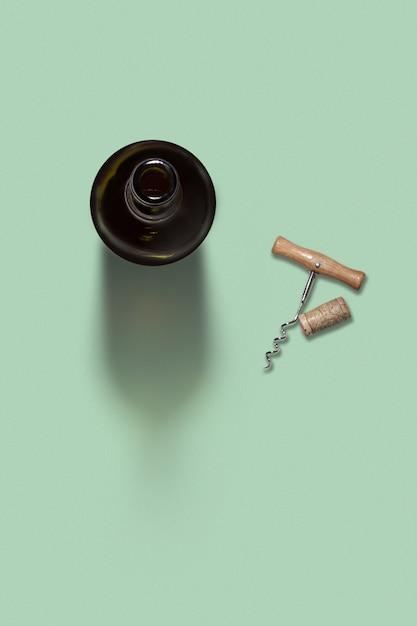 Alkohol trinken wein geöffnete flasche mit natürlichem korken und korkenzieher auf hellgrünem hintergrund mit weichen schatten und kopierraum. draufsicht. Premium Fotos