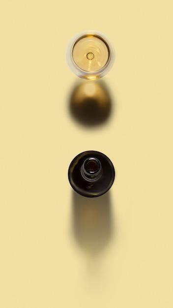 Alkoholgetränkset aus geöffneter weinflasche und glas weißwein auf hellgelbem hintergrund mit weichen schatten und kopierraum. draufsicht. Premium Fotos