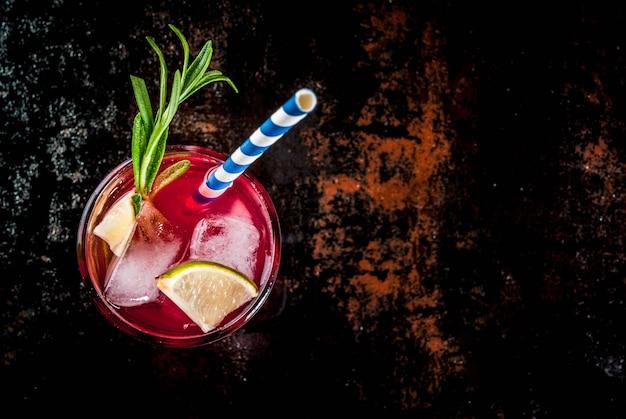 Alkoholisches cocktail der roten moosbeere und des kalkes der erfrischung mit rosmarin und eis, zwei glasdraufsicht Premium Fotos