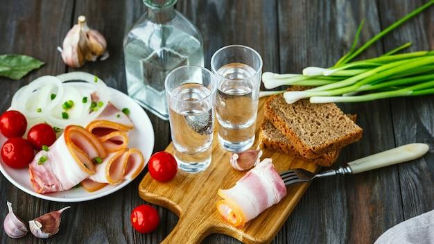 Alkoholisches getränk mit schmalz und frühlingszwiebeln auf holzwand. alkohol purer craft drink und traditionelle snacks, tomaten und toastbrot. negativer raum. feiern und lecker. Kostenlose Fotos