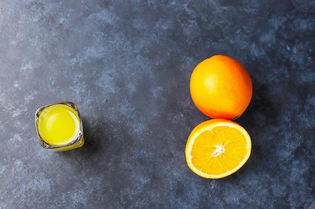 Alkoholisches orangensaftgetränk im schnapsglas mit orange scheibe und orange auf dunklem hintergrund Kostenlose Fotos