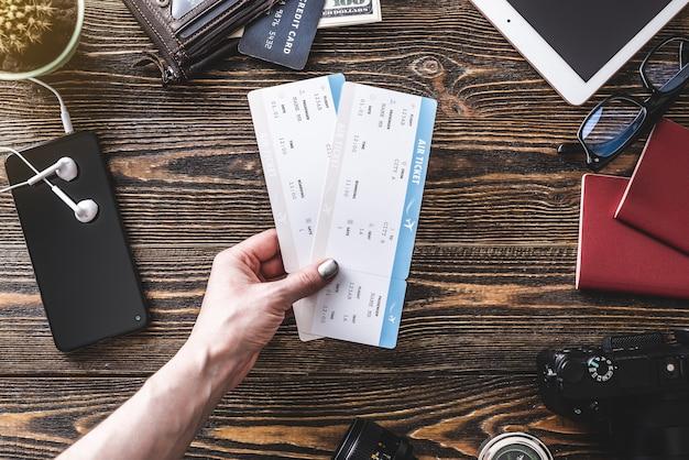 Alle notwendigen dinge für den flug im urlaub. flugtickets, reisepass, telefon und kreditkarte auf einem hölzernen hintergrund Premium Fotos