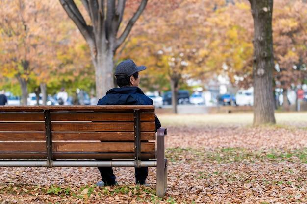 Allein älterer japanischer mann, der auf einer bank im park auf herbstsaison stillsteht Premium Fotos