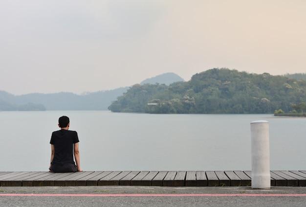 Allein junger mann, der auf dem hölzernen gehweg schaut zum berg im see mit sonnenuntergang sitzt Premium Fotos