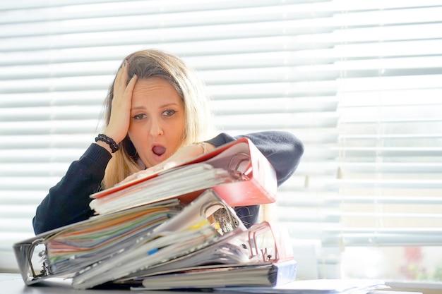 Alleine im büro mit vielen dokumenten arbeiten. schreien und schreien nach schlechten ergebnissen Premium Fotos